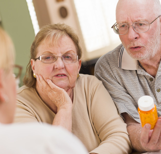 elderly women next to elderly man holding a prescription drug bottle conversing with a doctor