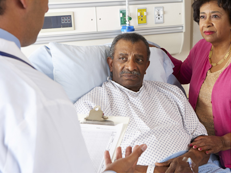 doctor holding a chart and conversing with an elderly man laying in a hospital bed and his wife