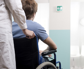 doctor pushing a patient in a wheelchair-through the hallway of a hospital
