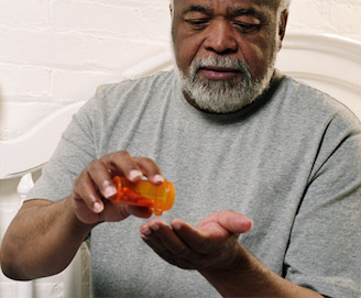 elderly man pouring pills from a pill bottle in to his hand
