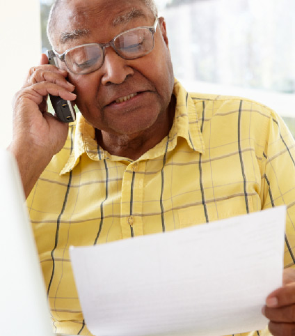 elderly man talking on the phone while holding papers