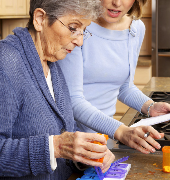 elderly woman and-daughter placing pills in a pill planner