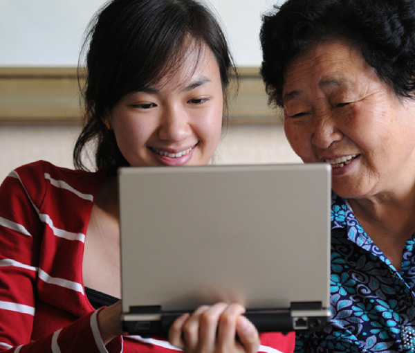 grandmother and grandaughter looking at a computer screen