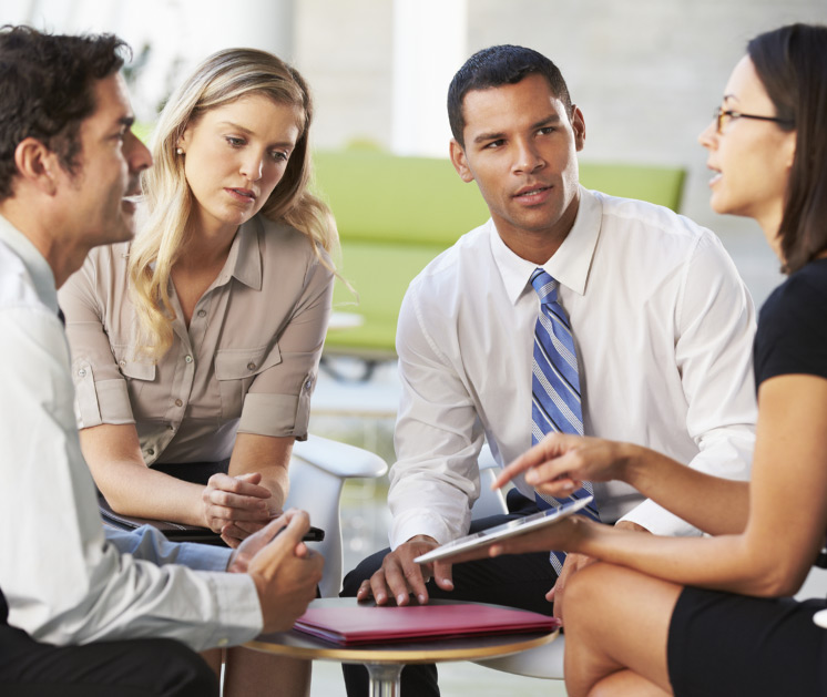 group of four young professionlas meeting around a table