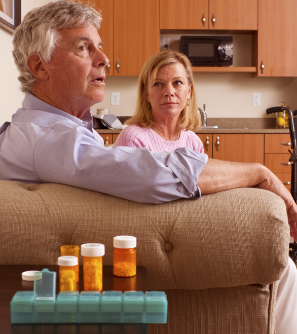 man and women sitting on a couch with medication bottles on the table