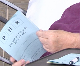 patient in hospital bed looking through-a-paper-booklet labled personal health record