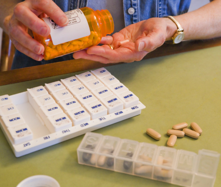 person pouring medication from a large bottle into their hand with pill box calendars and more medication sitting on the table in front of them