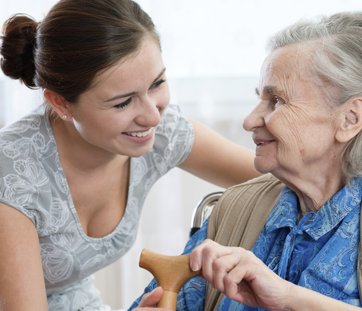 young woman smiling and conversing with elderly woman holding a cane
